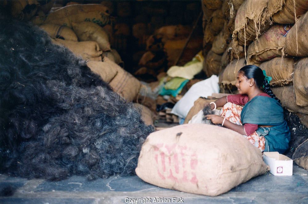 In a hair processing factory in the town of Eleru in the state of Andhra Pradesh a young girl sits in a warehouse sorting hair.