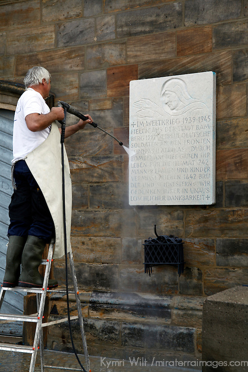 Europe, Germany, Bamberg. A man spray washes plaque on Old Town Bamberg building facade.