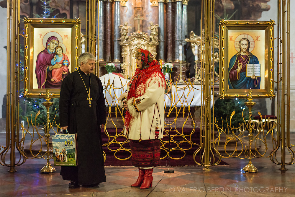 A woman in traditional costumes in a conversation with the priest in Cathedral of St. Clement