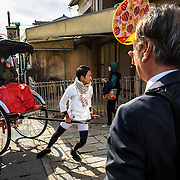 A guide pulls passengers in a rickshaw in Arashiyama, Kyoto, Japan.