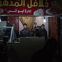 A felafel shop in the Al Shate' illuminated by the generators, northern Gaza City. Un negozio di felafel  illuminato dai generatori nel nord di Gaza City