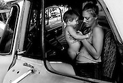 Amanda Barnes and her two-year-old son Brandon relax in their only vehicle, a pickup that is more often broken than not.