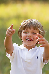 little boy outdoors smiling and pointing