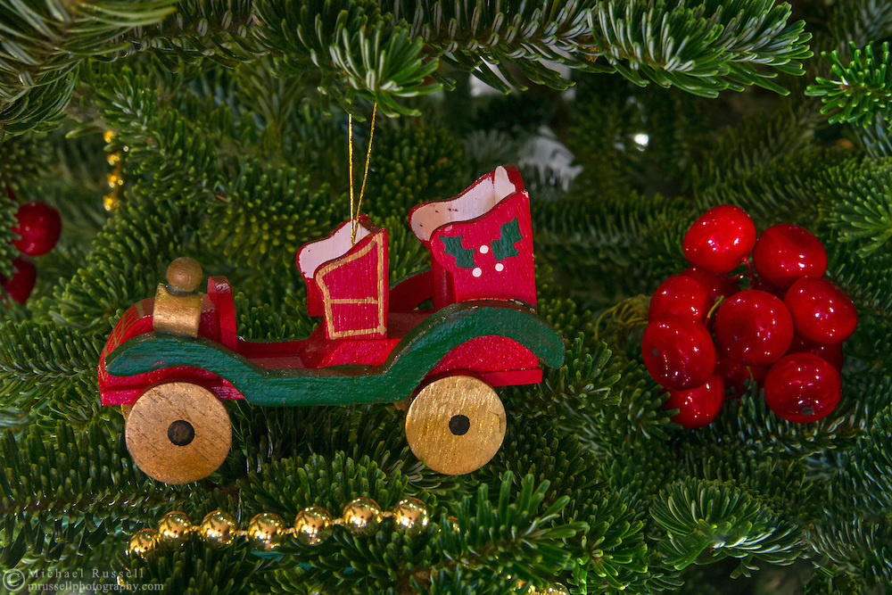 A toy car and berries on a Christmas tree