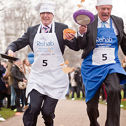 London, UK - 12 February 2013: the 16th Parliamentary Pancake Race takes place next to the Houses of Parliament on Shrove Tuesday raising money for the charity Rehab. Politicians and MPs toss pancakes into the air and catch them in the pan whilst running.The team of MPs has won the event this year.