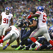 Seattle Seahawks player Marshawn Lynch has his helmet stripped by New York Giants player Jameel McClain (53) as Lynch is stopped at the goal line on Sunday, November 9, 2014 at CenturyLink Field in Seattle. The Seahawks defeated the Giants 38-17. (Joshua Trujillo, seattlepi.com)