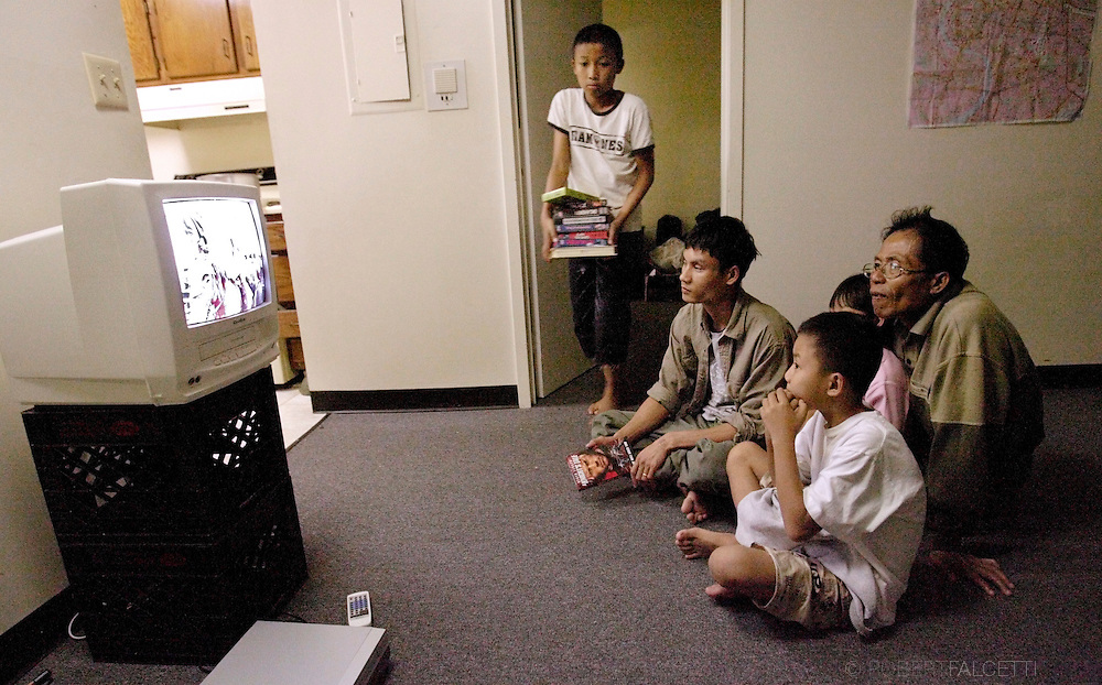 Lay Moo carries a stack of videos that had been donated to his family while fellow refugees Da Bu, Toe Toe Poe (Lay Moo's father) and La Lwe Say watch a John Wayne movie October 11, 2007.. (Photo by Robert Falcetti)