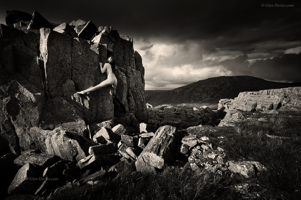 Nominated for 11th International B&amp;W Spider Awards<br /> <br /> <br /> After a two hour slog up from sea-level valley to mountain top, loaded with photo gear &amp; warm clothing, we were made to feel humble by a young woman climbing nude to the summit itself. Her pale soft skin contrasted with the sharp, rough rock but with such purpose, grace and balance, as if a slow motion dance, we could see her muscles working as she pulled, stepped into and lay-backed the arete before standing tall at the highest point to feel the cool mountain-top breeze caressing her hot skin. Below her, we huddled up and drank coffee and ate sandwiches.<br /> <br /> &ldquo;Although the nude is vital to the project and integral within the images, the images are not just &lsquo;nudes&rsquo; &ndash; they are landscapes and stories. In a way they are just simple, beautiful, dreamlike visual questions&rdquo;.
