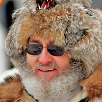 Fur hats, parkas, and warm smiles are worn by Eagle River resident Russ Wilmot, who volunteers each year at the ceremonial start of the Iditarod in downtown Anchorage. Over 1,800 volunteers assist in the Iditarod effort in Anchorage and throughout the state.