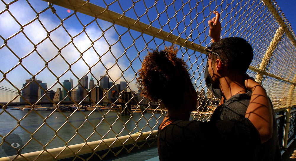 Abi Sara Machold and Shem Alleyne, both of Brooklyn, sadly watch the smoke billow over the southern end of Manhattan from the Manhattan Bridge.