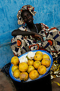 A young woman selling lemons in a street of Bijene, posing for a photograph.