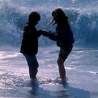 Children hold hands while facing the crashing waves of the Atlantic Ocean.