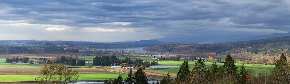 Panorama view of Glen Valley farmland in Langley and Abbotsford, the Fraser River, and Coquitlam/Burnaby Mountain beyond.  Photographed in the fall from the north end of Bradner Road in Abbotsford, British Columbia, Canada