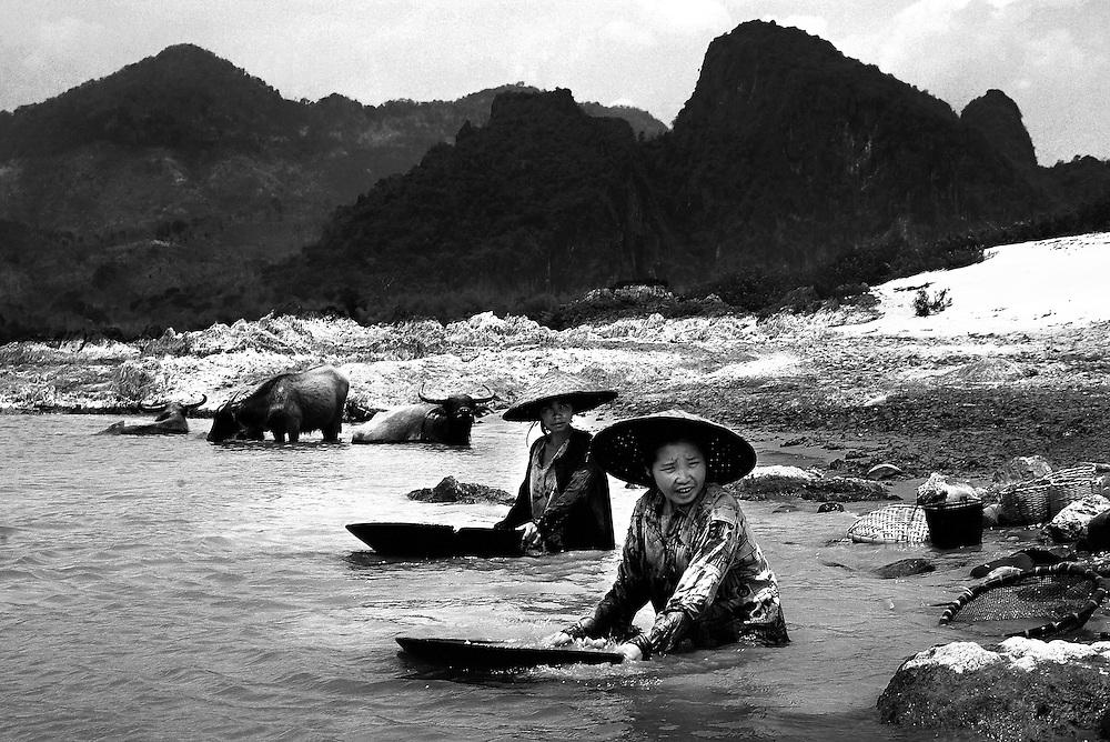 Women panning for gold on the Mekong River near Luang Prabang, Laos.