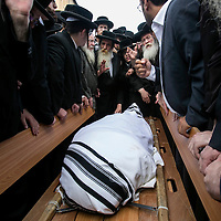 Ultra-Orthodox Jewish men gather around the body of Yeshayahu Kirshavski during his funeral in Jerusalem, Tuesday, Oct. 13, 2015. A pair of Palestinian men boarded a bus in Jerusalem and began shooting and stabbing passengers, while another terrorist rammed a car into a bus station before stabbing bystanders, in near-simultaneous attacks. <br /> Photo by Olivier Fitoussi.