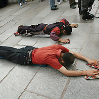 Pilgrims prostrate themselves in front of the Jokhang Temple, the most revered religious structure in Tibet. The Barkhor, Lhasa, Tibet. 8/6/05.