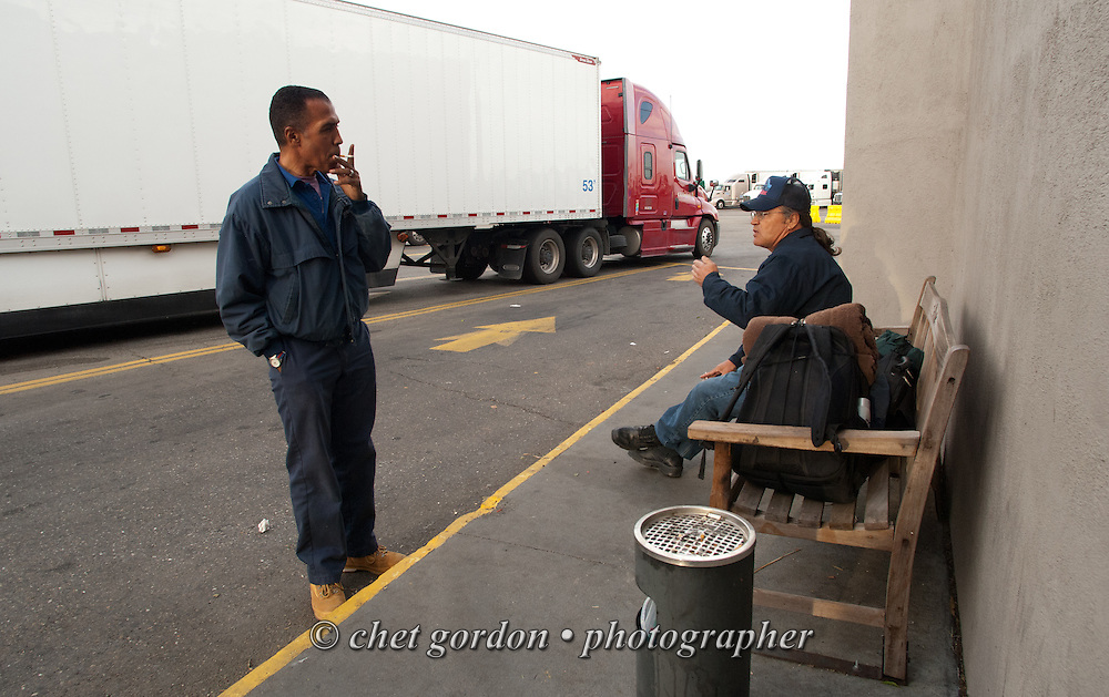 Over the road driver Jose Williams (left) speaks with a driver's helper at a truck stop in Santa Nella, CA on Friday, April 24, 2015. Williams, a cross country trucker with a national household moving company, made several delivery stops in central California's Bay Area during the week with loads that originated in Virginia on April 16th.  © Chet Gordon/THE IMAGE WORKS