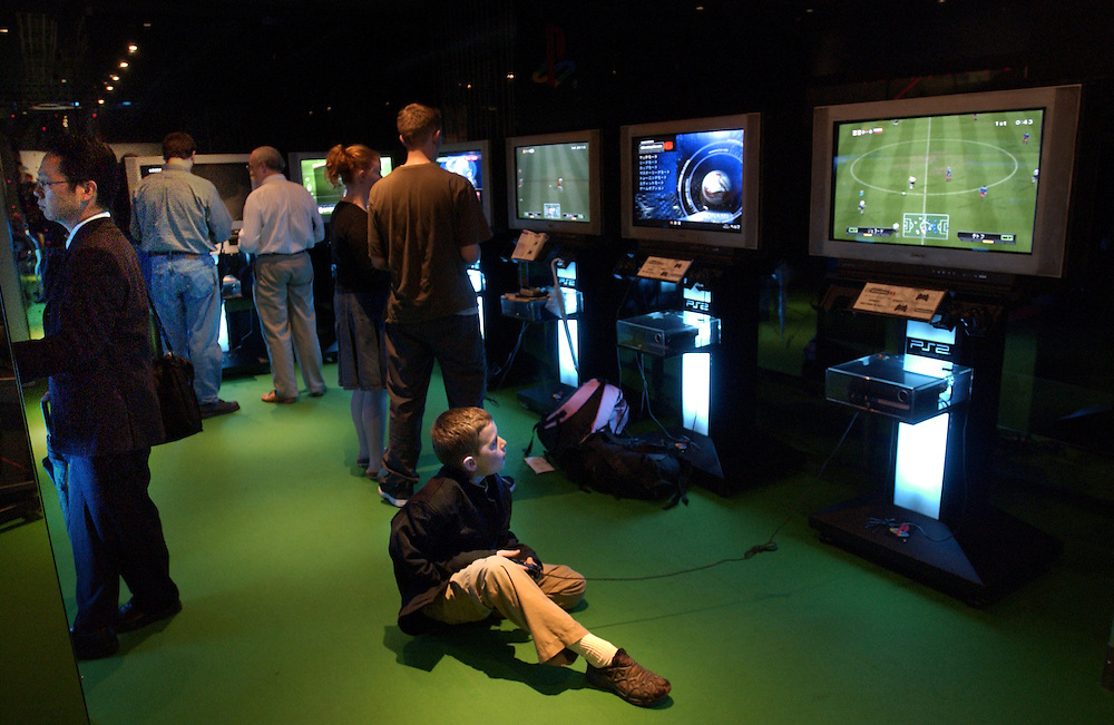A young boy takes time to play World Cup soccer on a playstation at the Sony Building in Ginza, Tokyo. Japan 25/06/02..©David Dare Parker/AsiaWorks Photography