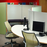 colourful curved office desk and seating space with computer terminals and chairs