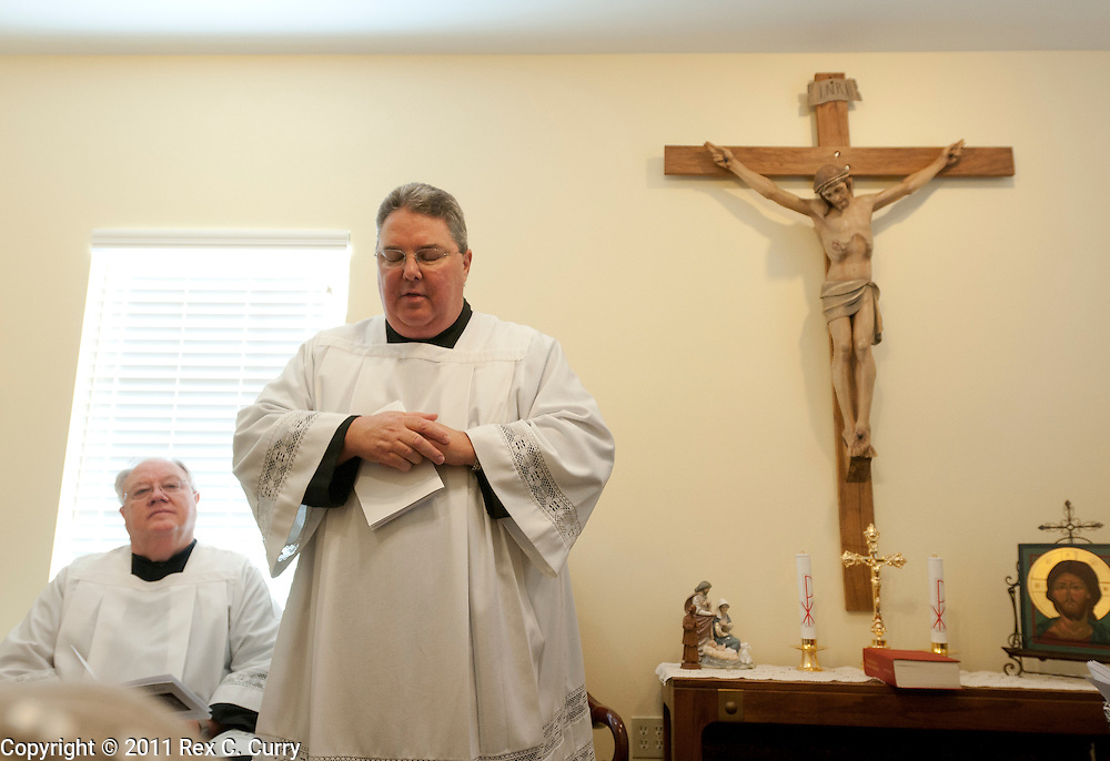 Father Charles Hough, foregound, leads his congregation in morning prayer at the St. John Vianney Parish in Cleburne, Tx. Sunday Jan. 1, 2012.  Hough is an Episcopal priest in the process of becoming ordained as a Catholic priest.  The parish is temporarily operating out of a private business. .