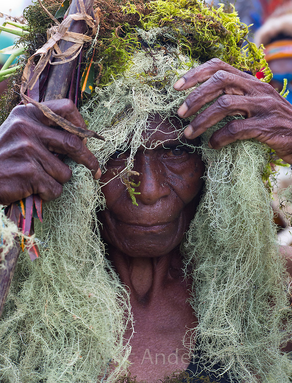 Portrait of an old woman dressed in a traditional tribal head dress made from moss and lichen. Photo taken at the Goroka Show, an annual Singsing Festival in the highlands of Papua New Guinea