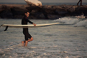 A surfer carries his board into the 91st surf break, Rockaway Beach, Queens, NY.