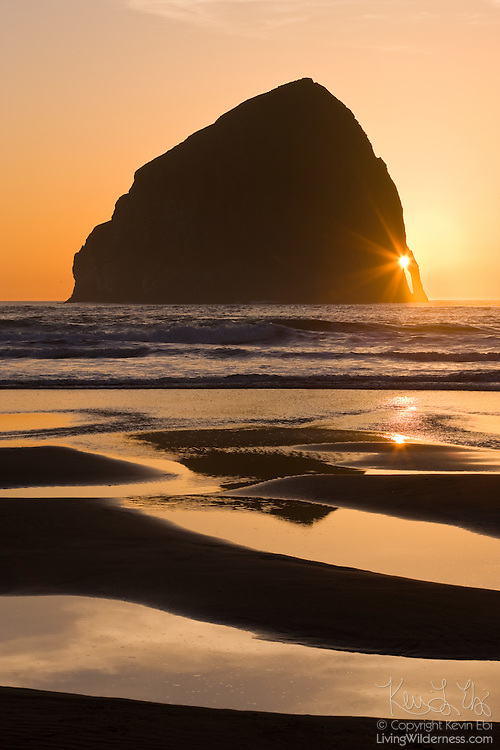 The setting sun shines through the arch of Haystack Rock, located off Cape Kiwanda on the Oregon Coast near Pacific City, Oregon.