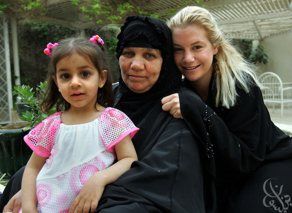 Humanitarian aid worker Marla Ruzicka (r)poses for a portrait with an Iraqi family her organization, the Campaign for Innocent Victims in Conflict (CIVIC) recently helped in a photograph taken a day before her April 16,2005 death in Baghdad, Iraq.  Ruzicka was apparently killed by a suicide bomber targeting a nearby American convoy on the airport road in Baghdad.
