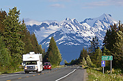 Alaska.  Camper driving along the Seward Hwy northbound  with mountains in the Chugach National Forest in the background.