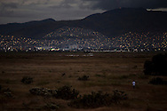 A man stands in the midddle of Lake Texcoco, an area which was once a lake is now a dumping ground for bodies in the drug war. In th edistance, New development moves up the mountainsides of Mexico City.
