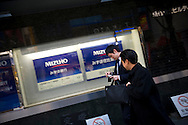 Businessmen walk near a branch of Mizuho in Tokyo, February 2, 2009. Mizuho Financial Group, Japan's second-largest bank, swung to a $565 million loss for the first nine months of the business year, hurt by losses on its stock portfolio and a weak economy, and it cut its full-year forecast again.