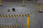 Brushes and bucket on the ground, surrounded by hazzard tape in Trafalgar Square, central London.