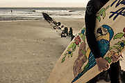 A surfer clutches his surfboard on the beach as another enters the water at 91 st. surf break, Rockaway Beach, Queens, NY.