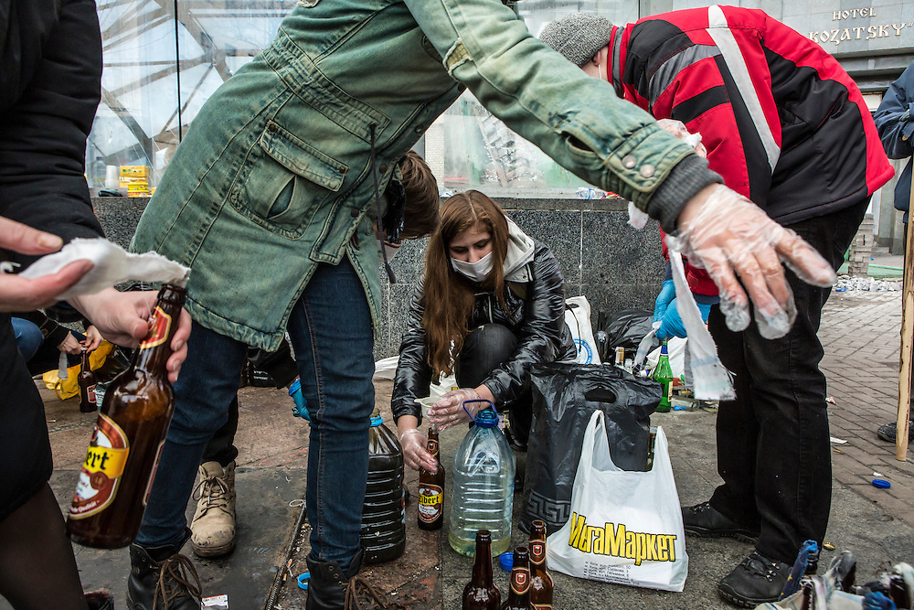 KIEV, UKRAINE - FEBRUARY 20: Women prepare Molotov cocktails for anti-government protesters near Independence Square on February 20, 2014 in Kiev, Ukraine. After several weeks of calm, violence has again flared between anti-government protesters and police, with dozens killed. (Photo by Brendan Hoffman/Getty Images) *** Local Caption ***