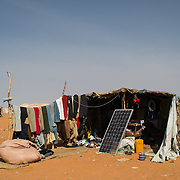 A shop selling used clothes and shoes at the Mbera refugee camp in southeastern Mauritania on 1 March 2013. The solar panel is used to charge mobile phones.
