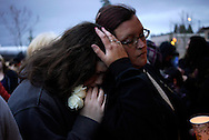 Sarah Halstead (R) comforts her daughter Allison at a candlelight vigil for mudslide victims in Arlington, Washington March 25, 2014. Rescue workers searched through mucky rubble on Tuesday with hopes dwindling of finding any more survivors from among scores of people still missing from a devastating weekend mudslide in Washington state that killed at least 14. REUTERS/Rick Wilking (UNITED STATES)