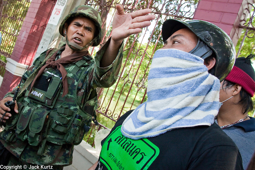 14 MAY 2010 - BANGKOK, THAILAND: Red Shirt protesters talk to Thai soldiers on a patrol at the intersection of Rama IV and Witthayu Roads in Bangkok Friday morning. Tensions among Red Shirt protesters demanding the dissolution of the current Thai government rose overnight after Seh Daeng, the Red Shirt's unofficial military leader was shot in the head by a sniper. Gangs of Red Shirts have taken over military checkpoints on Rama IV and are firing small rockets at military helicopters and army patrols in the area. Troops have responded by firing towards posters.  PHOTO BY JACK KURTZ