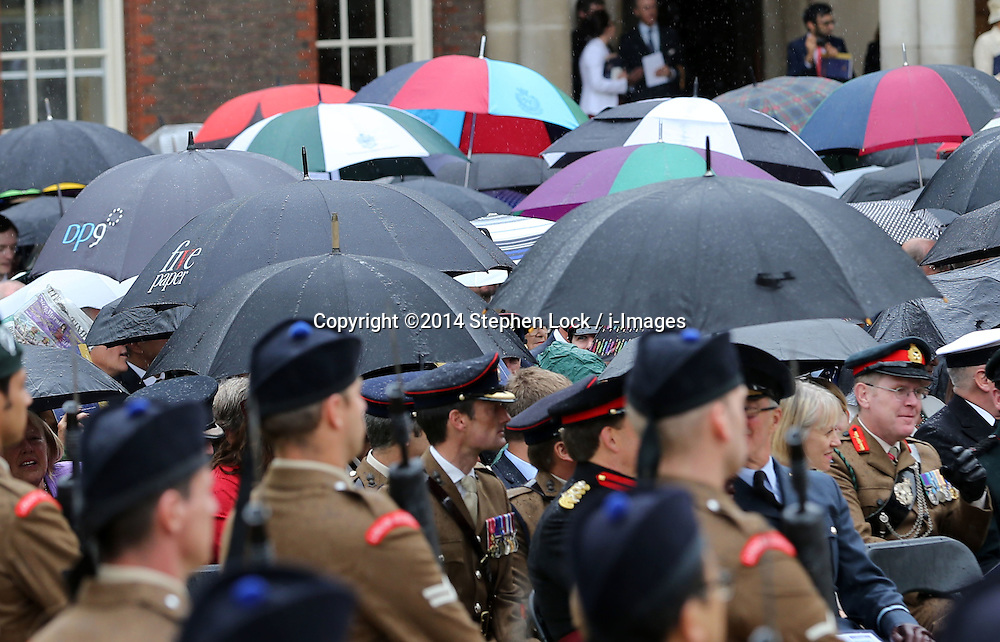 Image licensed to i-Images Picture Agency. 28/06/2014. London, United Kingdom. Umbrellas as the rain fell at the  Solemn Drumhead Service at the Royal Hospital Chelsea, London. The service was to commemorate those who volunteered to serve in the First World War on the Centenary of the assassination of Archduke Franz Ferdinand.  Picture by Stephen Lock / i-Images
