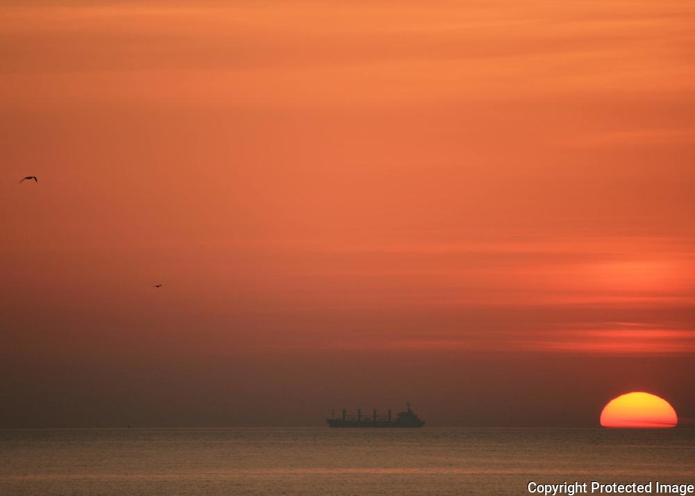 As the sun rises or sets on a firey sea, a cargo ship sails the horizon.