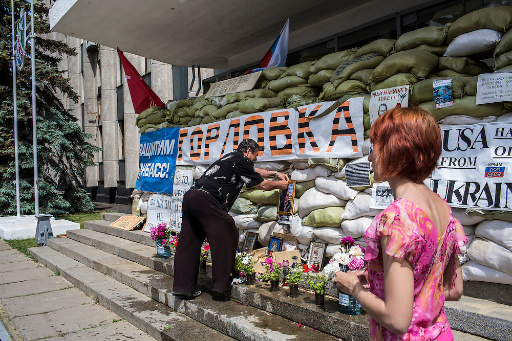 HORLIVKA, UKRAINE - MAY 24: Relatives of Aleksandr Politov, a pro-Russia militia fighter who was killed when his group attacked a Ukrainian military checkpoint two days earlier in the village of Blahodatne, place his photo outside the occupied city administration building on May 24, 2014 in Horlivka, Ukraine. Presidential elections are scheduled for tomorrow, but pro-Russia militias have been seeking to prevent them from being administered throughout the eastern part of the country. (Photo by Brendan Hoffman/Getty Images) *** Local Caption ***