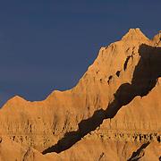The setting sun lights up several of the large sandstone fins that make up Badlands National Park in South Dakota.
