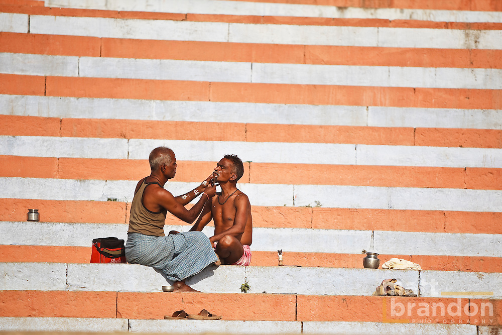 This man is receiving a morning shave from a barber on the steps of the river Ganges in Varanasi, India