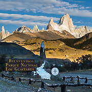 """A golden sunrise spotlights Mount Fitz Roy (3405 meters or 11,170 feet), which rises abruptly on the border between Argentina and Chile in the Southern Patagonian Ice Field in the Andes mountains. A sign saying Bienvenidos Parque Nacional Los Glaciares (""""welcome to The Glaciers National Park"""") greets visitors at the entrance to El Chaltén village, in Argentina, South America. In 1877, explorer Perito Moreno named """"Cerro Fitz Roy"""" for Robert FitzRoy (no space before the capital R) who, as captain of the HMS Beagle, had travelled up the Santa Cruz River in 1834 and charted much of the Patagonian coast. First climbed in 1952 by French alpinists Lionel Terray and Guido Magnone, Mount Fitz Roy has very fickle weather and is one of the world's most challenging technical ascents. It is also called Cerro Chaltén, Cerro Fitz Roy, and Monte Fitz Roy (all with a space before the R). Chaltén comes from a Tehuelche (Aonikenk) word meaning """"smoking mountain"""" (explained by frequent orographic clouds). Cerro is a Spanish word meaning hill. El Chaltén village was built in 1985 by Argentina to help secure the disputed border with Chile, and now tourism supports it, 220 km north of the larger town of El Calafate. The foot of South America is known as Patagonia, a name derived from coastal giants, Patagão or Patagoni, who were reported by Magellan's 1520s voyage circumnavigating the world and were actually Tehuelche native people who averaged 25 cm (or 10 inches) taller than the Spaniards. Mount Fitz Roy is the basis for the Patagonia company's clothing logo, after Yvon Chouinard's ascent and subsequent film in 1968."""