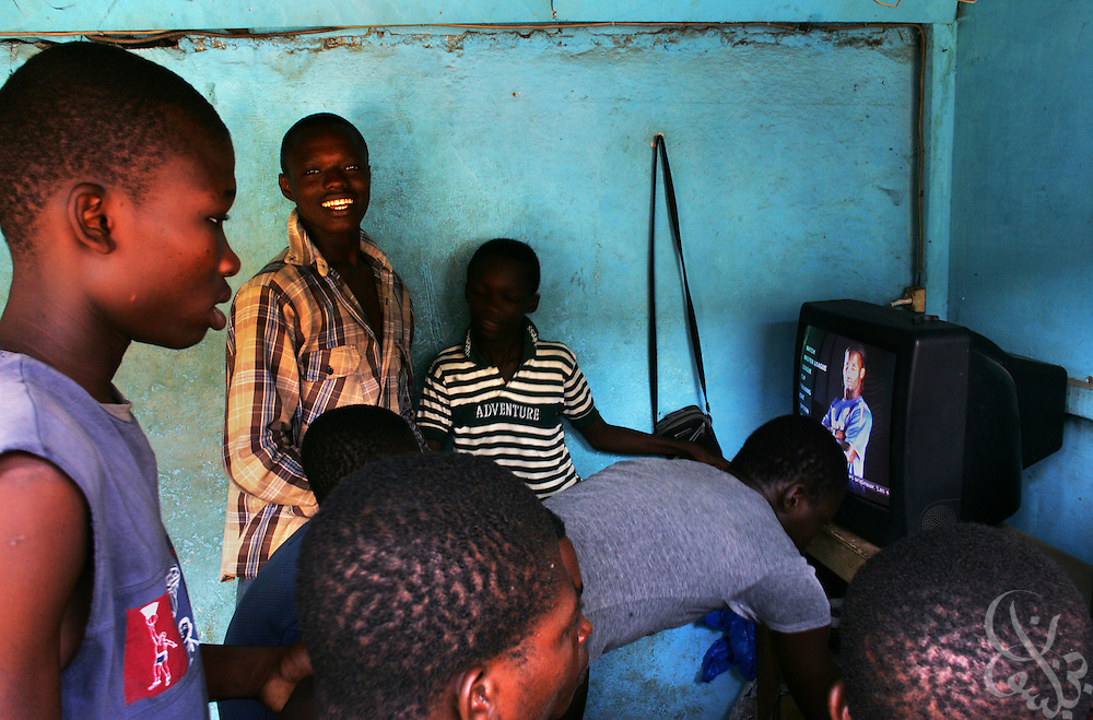 An image of Ivorian national team/Chelsea footballer Didier Drogba is seen on a television screen as Ivorian children play in a video arcade in the Adjame neighborhood of Abidjan, Ivory Coast February 17, 2006.  Ivorian children grow up dreaming of becoming players for Ivorian pro clubs, the national team, or in the European leagues.