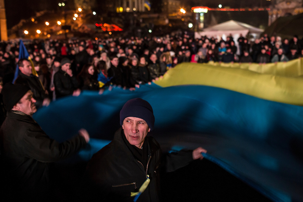 KIEV, UKRAINE - FEBRUARY 23: People wave a large Ukrainian flag in Independence Square on February 23, 2014 in Kiev, Ukraine. After a chaotic and violent week, Viktor Yanukovych has been ousted as President as the Ukrainian parliament moves forward with scheduling new elections and establishing a caretaker government. (Photo by Brendan Hoffman/Getty Images) *** Local Caption ***