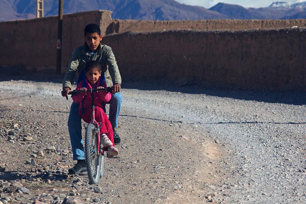 Africa, Morocco, Skoura. Kids on bike near Skoura.
