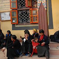 Tibetans sit outside near the stupa in Kathmandu.