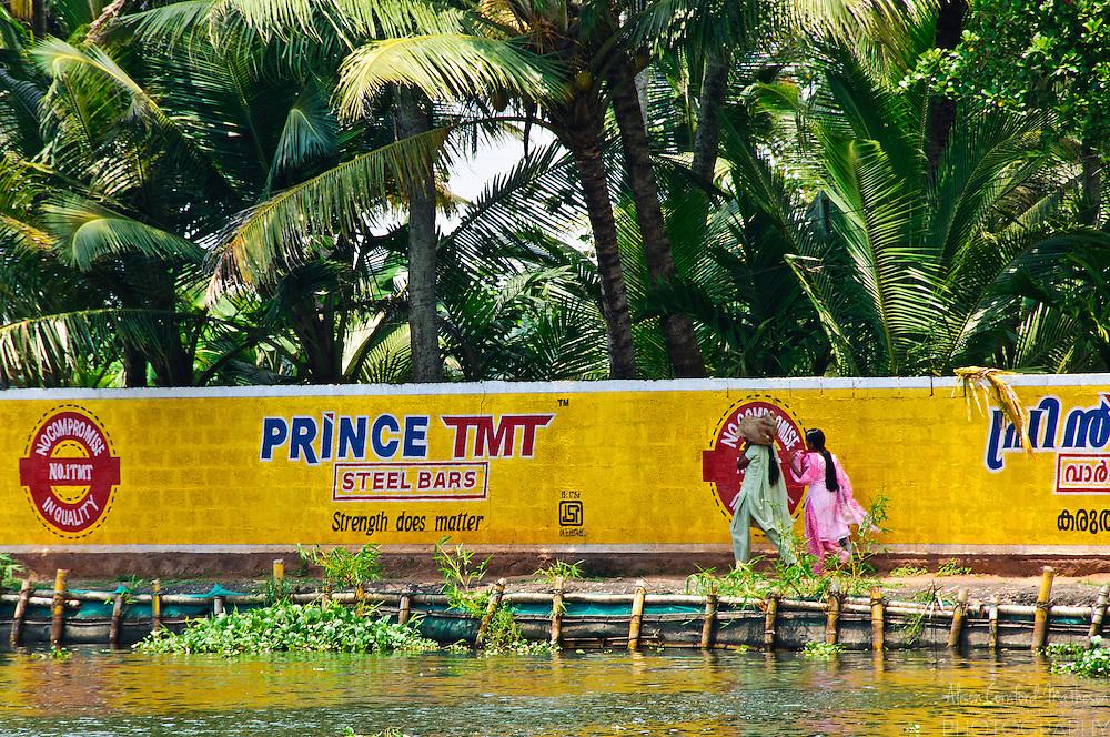 Two women walk beside bright advertising on the Kerala Backwaters.