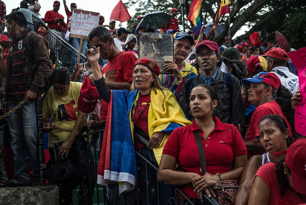 """CARACAS, VENEZUELA - JUNE 8, 2016: Loyalists to Venezuela's ruling socialist party who were given control of distributing government price-controlled food, participate in a rally in pouring down rain, by invitation of the President, at Miraflores, the presidential palace. Years of economic mismanagement, along with oil prices which fell to lows this year, have shattered Venezuela's food supply. In response, President Nicolás Maduro tightened has tightened his grip over the food supply. Using an emergency decree he signed in April, the president put most food distribution in the hands of a group of citizens brigades called C.L.A.P., loyal to leftists,  a measure critics say is reminiscent of food rationing in Cuba. """"They're saying, in other words, you get food if you're my friend, if you're my sympathizer,"""" said Roberto Briceño León, director of the Venezuelan Violence Observatory, a human rights group. PHOTO: Meridith Kohut"""