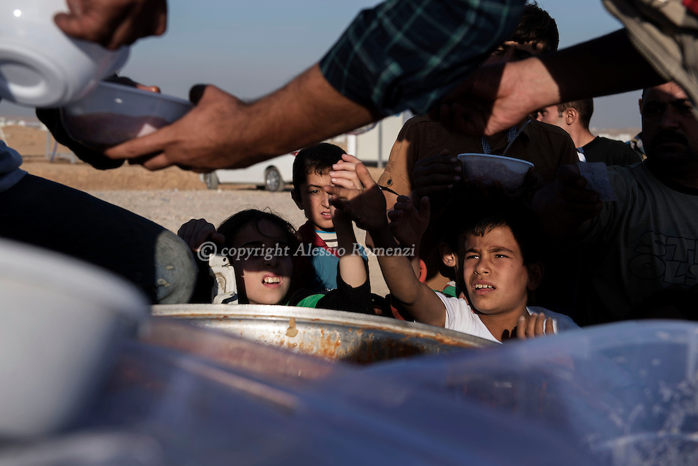 Iraq: People line up to receive food packages at an Assan Shame IDP camp in Al Kazir area on November 6, 2016. Alessio Romenzi